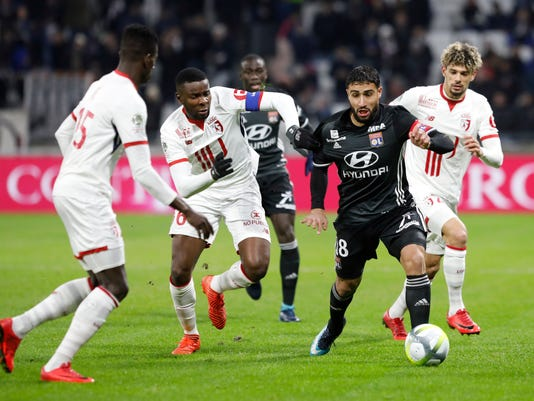 FILE - In this Wednesday, Nov. 29, 2017 file photo, Lyon's Nabil Fekir, right, challenges for the ball with Lille players during their French League One soccer match in Decines, near Lyon, central France. With Paris Saint-Germain streaking away at the top of the French league, the scrap for an automatic Champions League place promises to be an intense scrap between Monaco, Lyon and Marseille. (AP Photo/Laurent Cipriani, File)
