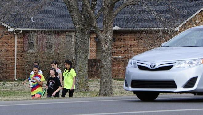 Students walk in front yards along Highway 96 West in Franklin because in some places there are no sidewalks.