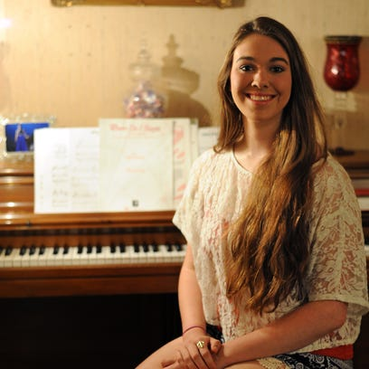 Zoe Fokakis sits in front of her family's piano.