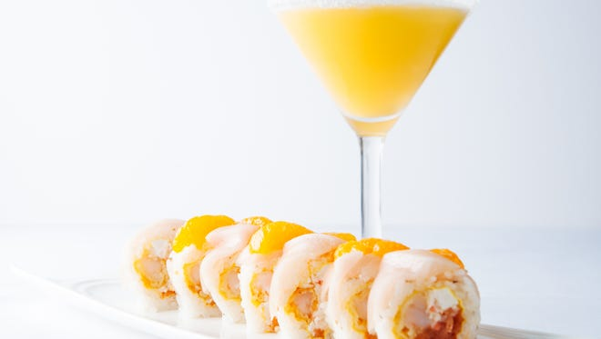 Made with shrimp tempura, spicy tuna, krab mix & cream cheese, yellowtail, mandarin oranges, and orange ginger vinaigrette, the Summer Lovin' roll is wrapped in soy paper and accompanied here by the Orange Julius martini.