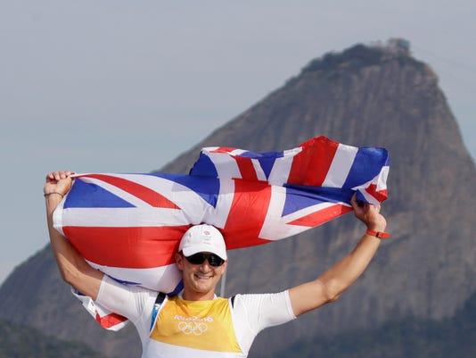Britain's Giles Scott celebrates winning the men's Finn sailing race at the 2016 Summer Olympics in Rio de Janeiro, Brazil, Tuesday, Aug. 16, 2016. (AP Photo/Gregorio Borgia)