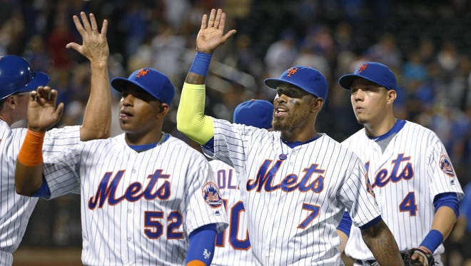 The Mets' Yoenis Cespedes, Jose Reyes and Wilmer Flores, from left, celebrate after the Mets defeated the Miami Marlins 7-4 Tuesday night at Citi Field.