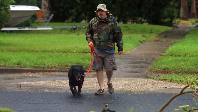 Jeff Taylor walks his dog Zeus as Hurricane Harvey becomes a category 4 hurricane in the Gulf of Mexico on Friday, Aug. 25, 2017, in Corpus Christi.