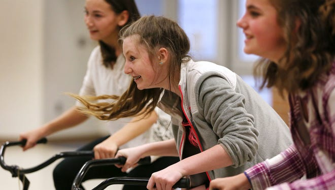 Avon Middle School North students, including Madison Turk, from left, Ashlee Plummer, and Tavi Goedeker enjoy cycling at full speed on stationary bikes as part of the Nine13sports program that is visiting their school. The bikes are connected to a computer to monitor their cycling, and they offer simulation as if they bike up hills and down hills increasing and decreasing in difficulty with the changes.  The youth health and fitness nonprofit company won a grant to expand their program.