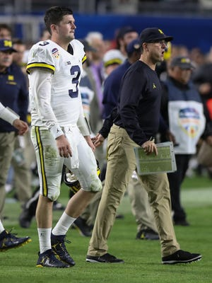 Quarterback Wilton Speight and coach Jim Harbaugh walk off the field after Michigan's 33-32 loss to Florida State in the Orange Bowl on Dec. 30, 2016 in Miami Gardens, Fla.