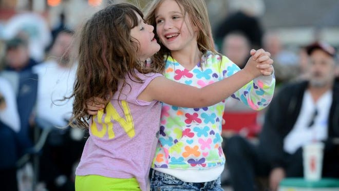 Cousins Chloe Beamer, left, and Madelyn Hughes dance to the sounds of After Midnight at the Gulfside Pavilion on Tuesday on Pensacola Beach during the first Bands on the Beach for the season. The event is a free, weekly outdoor concert series sponsored by the Santa Rosa Island Authority that continues through October.