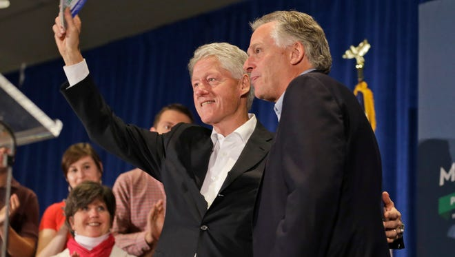 Former President Bill Clinton waves to the crowd along with Virginia Democratic gubernatorial candidate Terry McAuliffe during a rally at James Madison University in Harrisonburg, Va.