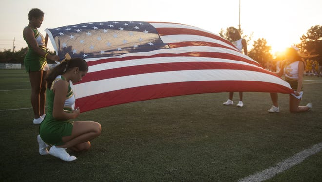 Camden Catholic cheerleaders display the American flag prior to last Friday night's football game between Camden Catholic and Camden, played at Camden Catholic High School in Cherry Hill.