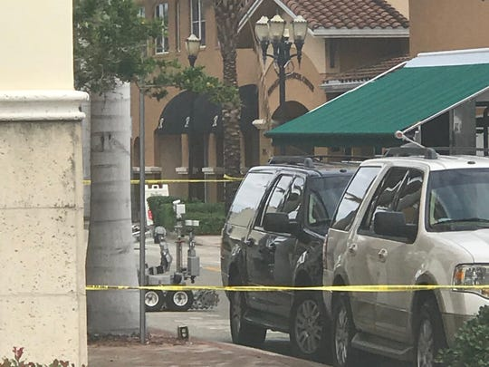 A bomb squad robot investigates a suspicious package at the the St. Lucie County Clerk of Courts building