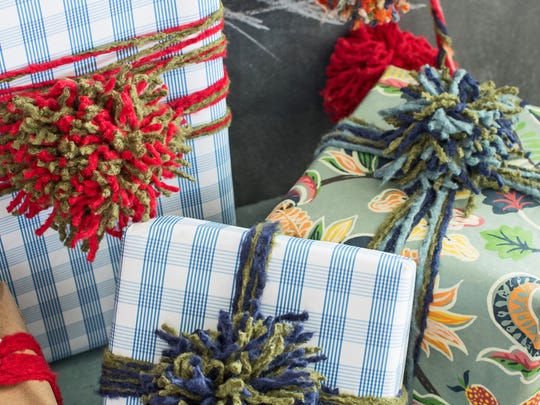 In this photo provided by HGTV, colorful yarn pom-poms adorn gift packages.