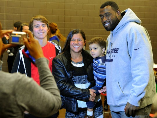 Camron Donaldson, his mother, Melissa Donaldson, and brother Caden Billings pose for a picture with Titans tight end Delanie Walker. Walker hosted his Turkey Bowl for single mothers at East Community Center on Tuesday.
