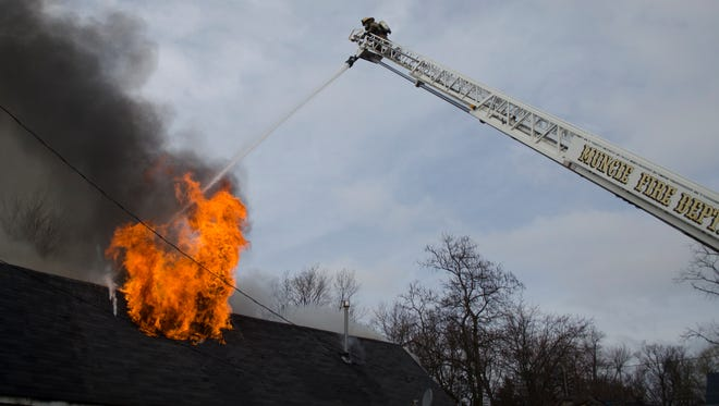 Muncie firefighters battle a blaze at a home in the 1100 block of West Second Street the afternoon of Friday, March 11, 2016. The home was also the location of a major methanphetamine bust in 2015.