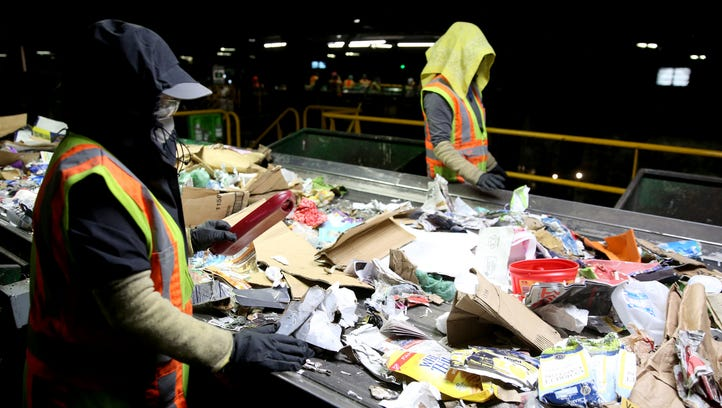 Recycling sorters pull non-recyclables off a conveyor