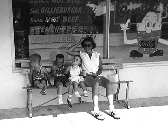 Doris Gilles, pregnant with her fourth child, sits on a bench outside Gilles with, from left, Jim, John and Mary Gilles.