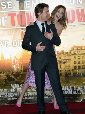 British actress Emily Blunt, background and US actor Tom Cruise pose for photographers at the Edge Of Tomorrow World Premiere at BFI IMAX in London, Wednesday, May 28, 2014, the first of three premieres covered in one day, with Paris and New York the other destinations. (Photo by Jon Furniss/Invision/AP) ORG XMIT: LJF101