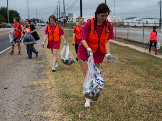 Anne Barry, a UL student, places a piece of litter into a garbage bag as fellow students participate in the UL Big Even along Cameron Street in Lafayette Saturday.