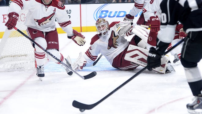 Dec. 20, 2014: Arizona Coyotes goalie Devan Dubnyk (40) and center Martin Hanzal (11) and defenseman Keith Yandle (3) defend a shot on goal by Los Angeles Kings left wing Tanner Pearson (70) in the first period of the gameat Staples Center.