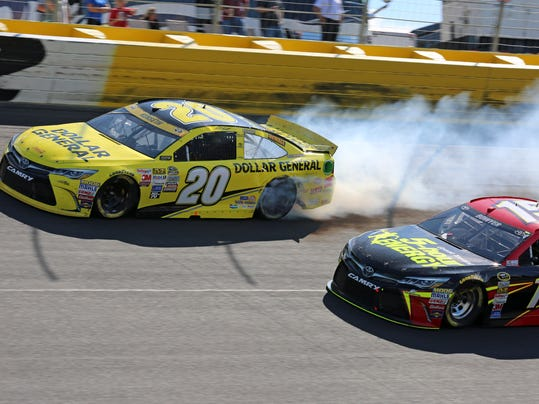 Smoke comes from the back of the car of Matt Kenseth (20) after hitting the wall during the NASCAR Sprint Cup series auto race at Charlotte Motor Speedway in Concord, N.C., Sunday, Oct. 11, 2015. (AP Photo/Jim Topper)