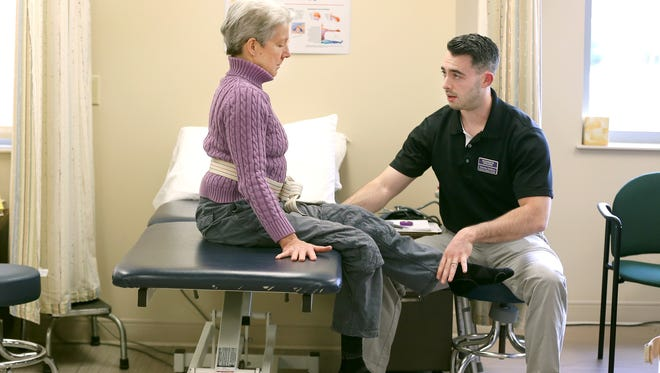 Nicholas DeMarco, a physical therapy graduate student at Nazareth College, does an assessment of a patient. The physical therapy program at the Pittsford college is flourishing and has strong community support.