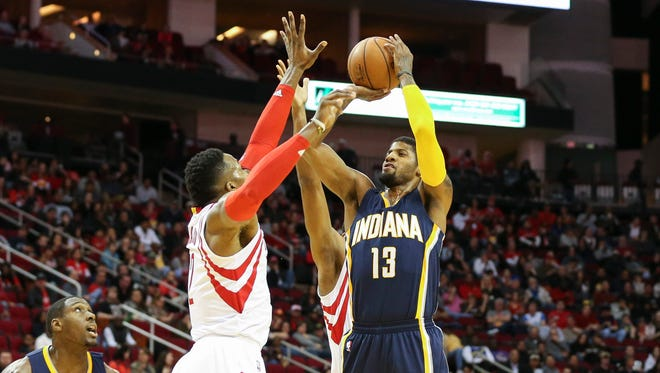 Indiana Pacers forward Paul George (13) shoots the  ball as Houston Rockets center Dwight Howard (12) defends during the first quarter at Toyota Center.
