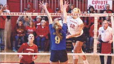 USD's Kendall Kritenbrink (12) spikes the ball past SDSU's Carley Gerving during Tuesday's match in Vermillion. The Coyotes won 25-12, 25-16, 25-16.
