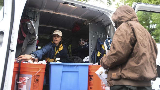 Homeless Gear staff member Linda Nuss reaches for a water bottle to give a homeless individual out of the organization's van on Tuesday, May 19, 2015, outside Old Town Library in Fort Collins, CO.