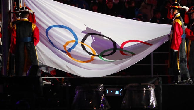The Olympic flag is lowered during the closing ceremony.