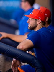 Tim Tebow looks out from the home dugout before his