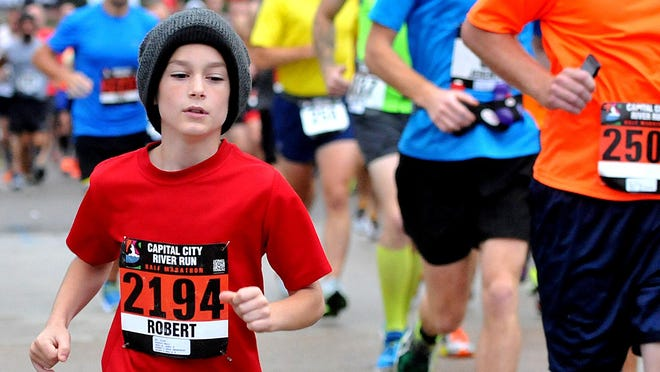 Nine year-old Robert Weil from Lansing, runs in the 2014 Capital City River Run and finishes with a time of 2:22:47 for the half marathon Sunday, September 21, 2014.