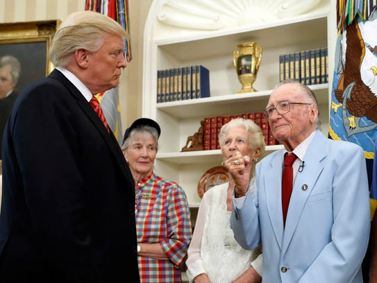 President Donald Trump listens to USS Arizona survivor