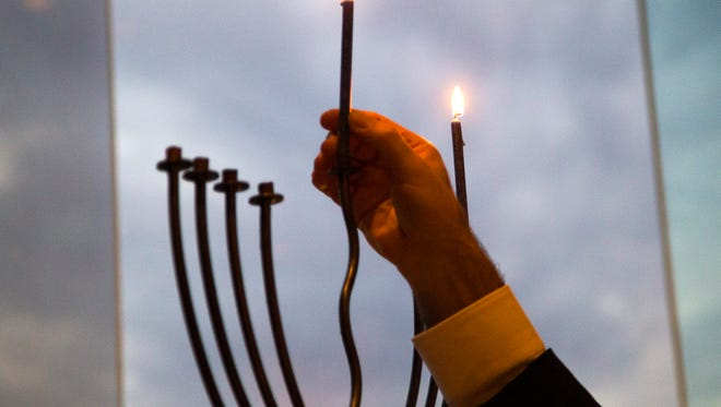The first candle is lit to mark the start of Hanukkah.