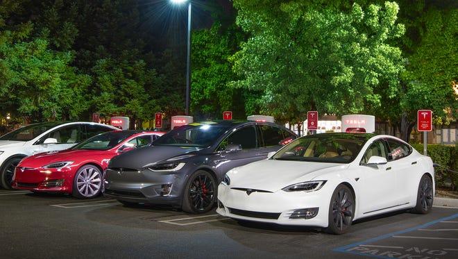 Various Tesla models parked at a Supercharger station.