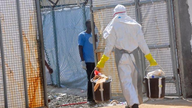 A Ebola health worker removes rubbish   from the Island Clinic Treatment center in Monrovia, Liberia.