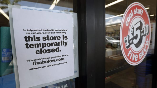 A sign is posted on a closed store, Thursday, April 23, 2020, in North Miami, Fla. A half million Floridians applied for unemployment benefits last week, as a statewide task force continues examining when businesses shuttered because of the new coronavirus can reopen.