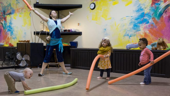 Instructor Nicole Newmaster gives the kids (from left) Henry Squire, 1, Tierstiana Buie, 2, and Laurilyn Humbane, 2, pool noodles to play with during the Mommy and Me class at D'Alto Studio.