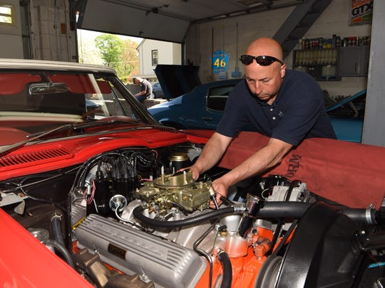 Kenny Pascoe of the Town of Poughkeepsie works on a 1966 Chevy Corvette convertible, one of the cars he has collected.
