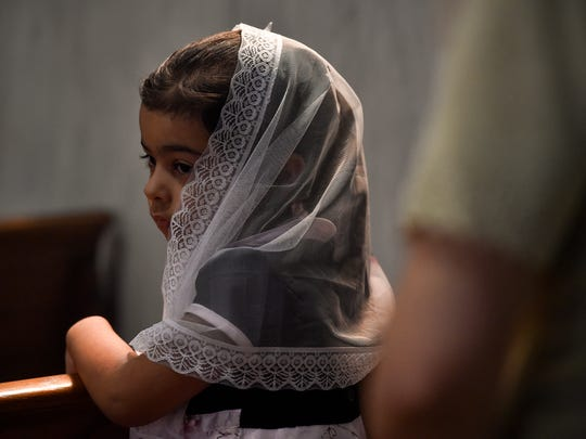 Loura Ibrahim, 3, wears a lace head covering during a Coptic Orthodox service Saturday, July 15, 2017, at St. Mary's Catholic Church in York. During the service, Coptic women and girls wear head coverings, often decorated with a cross or an icon of a saint.