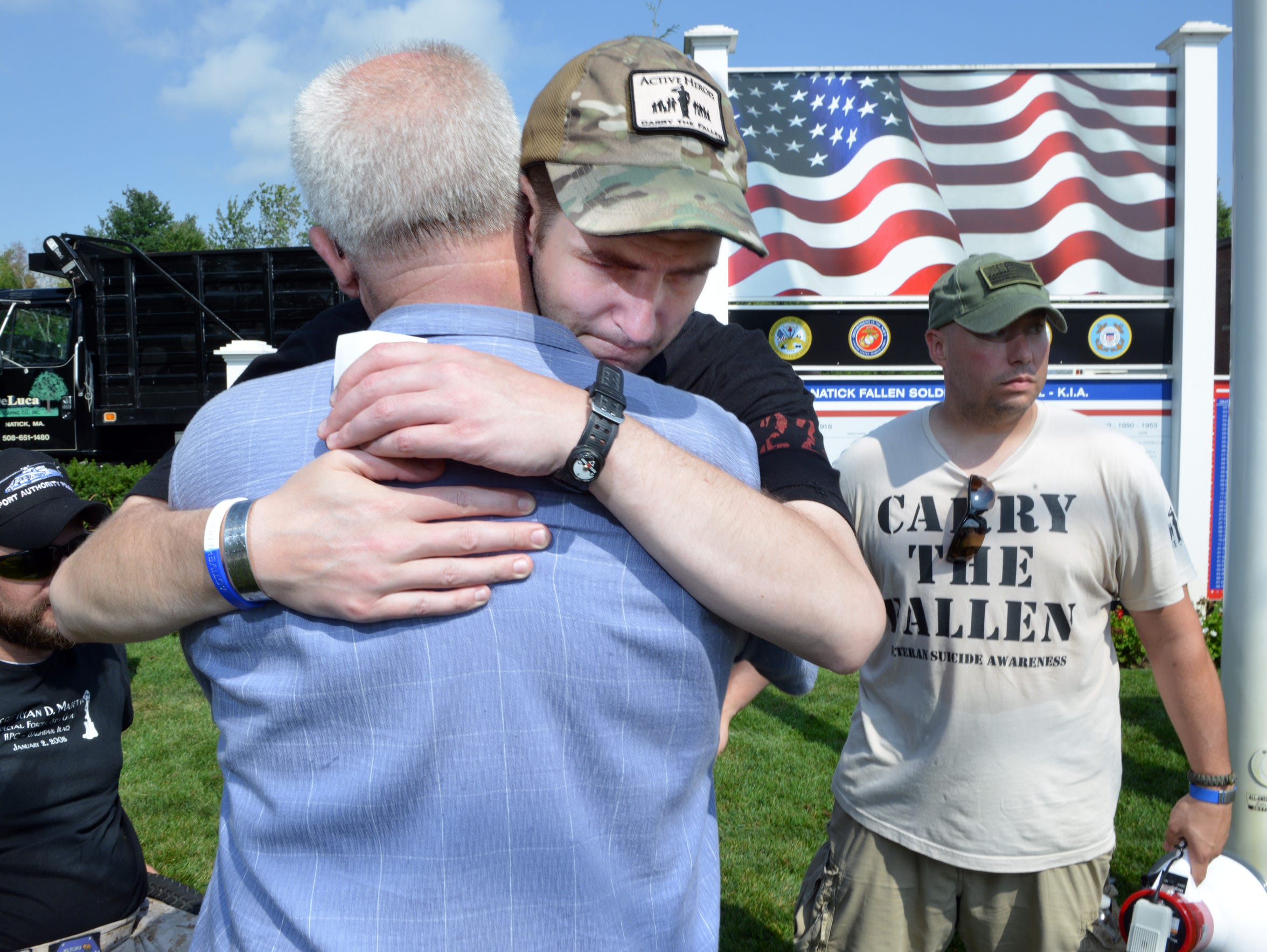 Army Capt. Justin Fitch, center, embraces Paul Carew,