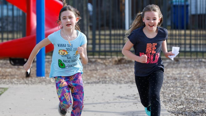 Students Ashlyn Loomans, left, and Madison Murphy, run  to the finish line April 4 during Girls on the Run program at Franklin Elementary School in Wausau, WIsconsin. On their hands are notes collected each time they completed a lap.