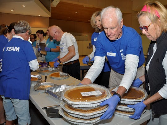 Bill Hollister and Linda Rounding bring out pumpkin pies for cutting into portions for Feeding the 5,000, a charitable community outreach of Lamb of God Church.