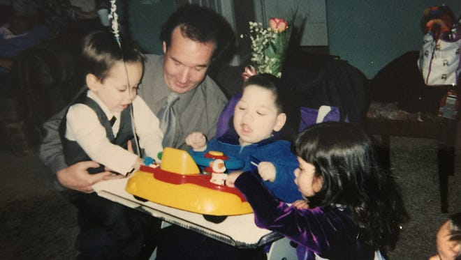Brandon Rowin (center) gets attention from his siblings and Arizona Republic reporter Scott Craven during the quads' third birthday party on Jan. 9, 2001. That's also the day the children were adopted by three families.