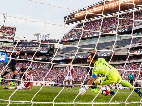 USA forward Clint Dempsey (No.8) puts a shot past Paraguay keeper Justo Villar (No. 1) in the first half of the USA's 1-0 win over Paraguay in their Copa America Group A game at Lincoln Financial Field in Philadelphia on Saturday evening.