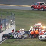 Kyle Busch, center, is taken to an ambulance on a stretcher after he was involved in a multi-car crash during the Xfinity series auto race at Daytona International Speedway, Saturday, Feb. 21, 2015, in Daytona Beach, Fla. (AP Photo/John Raoux)