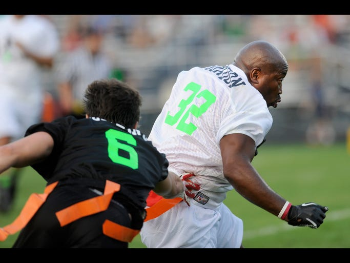 Team MusclePharm player Jay Azeltine times to grab the flag off Team sKeven player Terome Gordon during a flag football benefit on Thursday, July 31, 2014, at Granville High School. The benefit raised funds for melanoma cancer research. Gordon works for the Columbus Fire Department with Mark Rine, Mark, who has melanoma, and his brother Kevin Rine organized the event.
