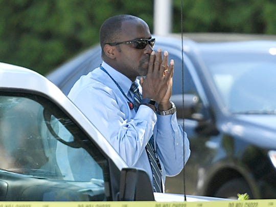 A man is watching behind the crime tape following an