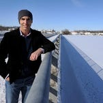 Geist Half Marathon co-founder and president Matt Troyer stands on the Olio Road bridge, which spans Geist Reservoir in Fishers. The middle of the bridge is the starting line for both the half-marathon and 5K coming up May 17.