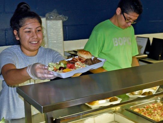Andrea Lira and Carlos Jimenez serve healthy meals.