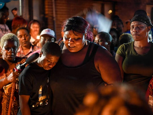 Deberianah Begley's brother Danquan and mother Tika Begley comfort each other as a crowd gathers for a candlelight vigil at the James Cayce Public Housing Development in Nashville, Tenn., Monday, Oct. 9, 2017.