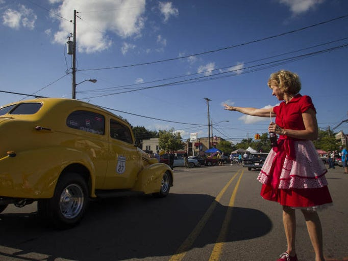 Linda Hundt of DeWitt's Sweetie-Licious greets participants Wednesday, August 20, 2014, entering downtown DeWitt on an Old US 27 Motor Tour stop.