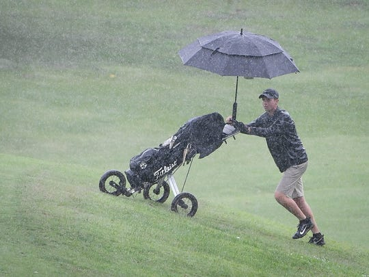 Golfing in heavy rain, North High graduate Owen Price pushes his clubs up to the eighteenth hole as he competes in the second round of the Courier & Press Men's City Golf Tournament at Helfrich Hills Golf Course Sunday, August 6, 2017.